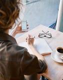 Mujer con el cuaderno en café Foto de archivo libre de regalías