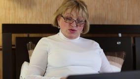 Mujer con el cuaderno La mujer mayor comunica con el ordenador portátil metrajes