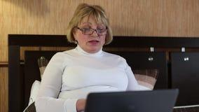 Mujer con el cuaderno La mujer mayor comunica vía el ordenador portátil almacen de metraje de vídeo