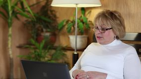 Mujer con el cuaderno La mujer mayor comunica vía el ordenador portátil metrajes