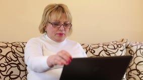 Mujer con el cuaderno La mujer mayor mecanografía el texto usando el ordenador portátil metrajes