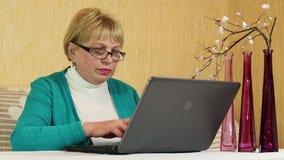 Mujer con el cuaderno La mujer mayor mecanografía el texto usando el ordenador portátil almacen de metraje de vídeo