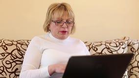 Mujer con el cuaderno La mujer mayor mecanografía el texto usando el ordenador portátil almacen de video