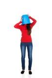 Mujer con el cubo plástico en la cabeza Fotografía de archivo