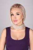 Mujer con el cuello atado por su pelo Cierre para arriba Fondo gris Foto de archivo