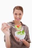 Mujer con el cuenco de ensalada que ofrece alguno Imágenes de archivo libres de regalías