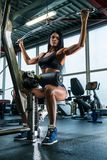 Mujer con el cuerpo atlético hermoso que hace los ejercicios para la parte posterior en máquina del cabel foto de archivo