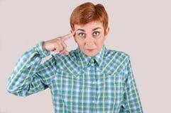 Mujer con el dedo índice en su cabeza Foto de archivo