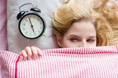 Mujer con el despertador Imagenes de archivo