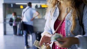 Mujer con el dinero cerca de la taquilla metrajes