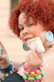 Mujer con el dinero rojo de la explotación agrícola del pelo rizado Foto de archivo libre de regalías