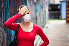 Mujer con el dolor de cabeza que lleva una mascarilla imágenes de archivo libres de regalías