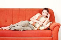 Mujer con el dolor de cabeza que pone en el sofá Foto de archivo