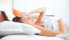 Mujer con el dolor de cabeza, temperatura en cama fotografía de archivo libre de regalías