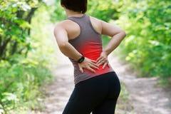 Mujer con el dolor de espalda, inflamación del riñón, lesión durante entrenamiento imagen de archivo
