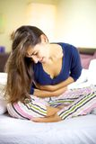 Mujer con el enfermo del problema del estómago en cama Imagen de archivo libre de regalías