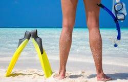 Mujer con el equipo que bucea que se coloca en una playa Imagen de archivo libre de regalías