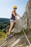 Mujer con el equipo que sube que se coloca en roca Imagen de archivo libre de regalías