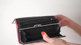 Mujer con el esmalte de uñas rojo que abre su monedero vacío metrajes
