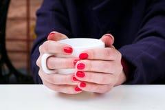 Mujer con el esmalte de uñas rojo que sostiene la taza blanca en un cafee Fotografía de archivo libre de regalías