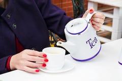 Mujer con el esmalte de uñas rojo que vierte una camiseta en una taza en un cafee Imagen de archivo libre de regalías
