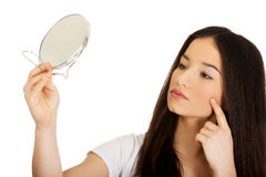 Mujer con el espejo que comprueba espinillas Fotografía de archivo libre de regalías
