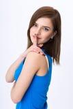 mujer con el finger que se sostiene secreto sobre los labios Fotos de archivo libres de regalías
