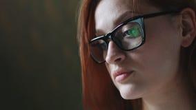 Mujer con el funcionamiento de vidrios en el ordenador portátil almacen de metraje de vídeo
