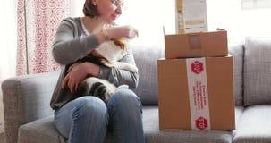 Mujer con el gato casero y el alimento para animales real de Canin almacen de metraje de vídeo