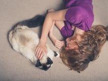Mujer con el gato en la alfombra Foto de archivo