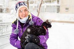 Mujer con el gato negro en nieve Imagen de archivo
