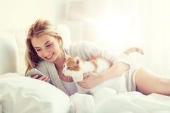 Mujer con el gato y smartphone en cama en casa Fotografía de archivo libre de regalías