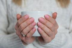 Mujer con el gel del pulimento de clavos del color de los rosas bebés en los fingeres que sostienen la taza de té fotografía de archivo