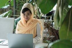 Mujer con el hijab que trabaja usando el ordenador port?til imágenes de archivo libres de regalías