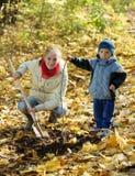 Mujer con el hijo que reajusta el árbol en otoño Foto de archivo