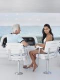 Mujer con el hombre envejecido centro que se sienta en el timón del yate Foto de archivo libre de regalías