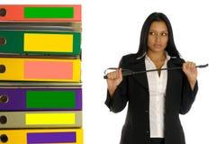Mujer con el interruptor cerca de la pila de documentos Fotografía de archivo libre de regalías