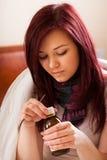 Mujer con el jarabe de consumición de la gripe Foto de archivo libre de regalías