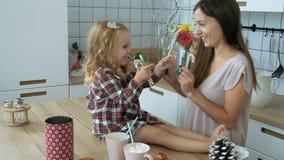 Mujer con el juego de la niña con el bastón de caramelo de la Navidad almacen de video