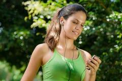 Mujer con el jugador mp3 que escucha la música Imagenes de archivo