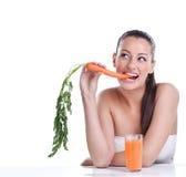 Mujer con el jugo de zanahorias Imágenes de archivo libres de regalías