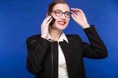 Mujer con el lápiz labial rojo en su teléfono de la mano Imágenes de archivo libres de regalías