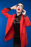 Mujer con el lápiz labial rojo en su teléfono de la mano Foto de archivo libre de regalías