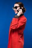 Mujer con el lápiz labial rojo en su teléfono de la mano Imagen de archivo libre de regalías