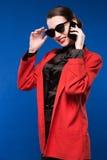 Mujer con el lápiz labial rojo en su teléfono de la mano Fotos de archivo libres de regalías