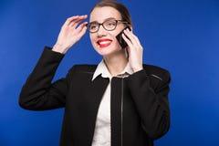 Mujer con el lápiz labial rojo en su teléfono de la mano Fotografía de archivo libre de regalías