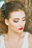 Mujer con el lápiz labial rojo y maquillaje coloreado, retrato en naturaleza Mirada al lado Sus ojos cubiertos Imagen de archivo libre de regalías