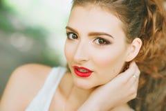 Mujer con el lápiz labial rojo y maquillaje coloreado, retrato en naturaleza Mirada de la cámara Fotos de archivo