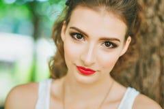 Mujer con el lápiz labial rojo y maquillaje coloreado, retrato en naturaleza Mirada de la cámara Imagen de archivo