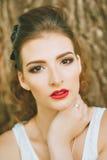 Mujer con el lápiz labial rojo y maquillaje coloreado, retrato en naturaleza Mirada de la cámara Fotografía de archivo libre de regalías